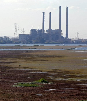A boat is seen stranded in the mud at low tide on the River Nile in front of a South Cairo Electricity Distribution Company power station in Cairo