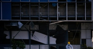 A police officer searches for evidence after a bomb blast at a Court building in Athens
