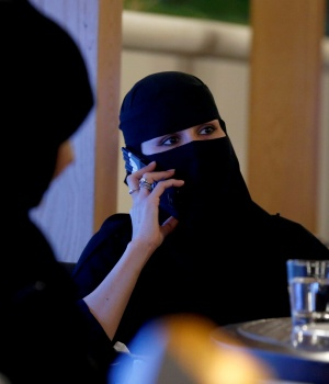 A woman speaks on a mobile phone in a cafe in Riyadh