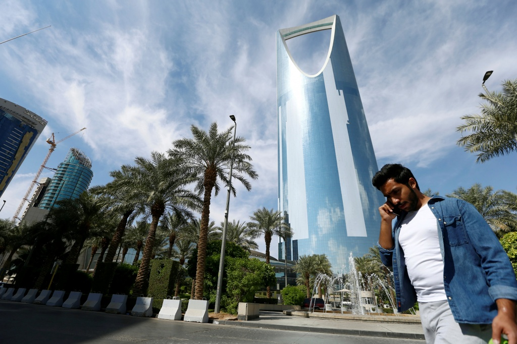 A man speaks on the phone as he walks past the Kingdom Centre Tower in Riyadh