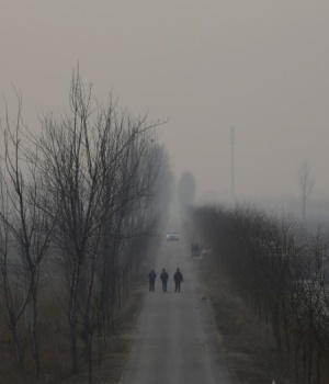 People walk along a village road on a polluted day on the outskirts of Langfang