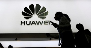 People walk past a sign board of Huawei at CES Asia 2016 in Shanghai