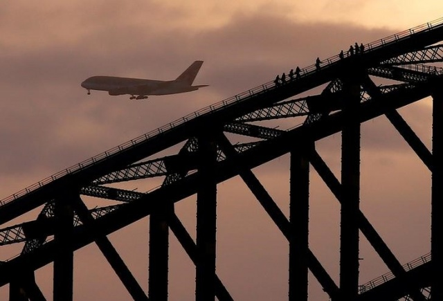 A plane prepares to land at Sydney International Airport behind climbers on the Sydney Harbour Bridge at sunset in Australia