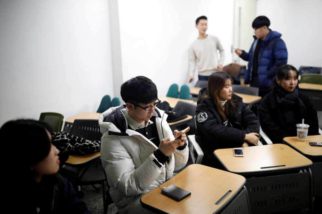 Eoh Kyung-hoon, leader of a club studying cryptocurrencies, checks his mobile phone after a meeting at a university in Seoul