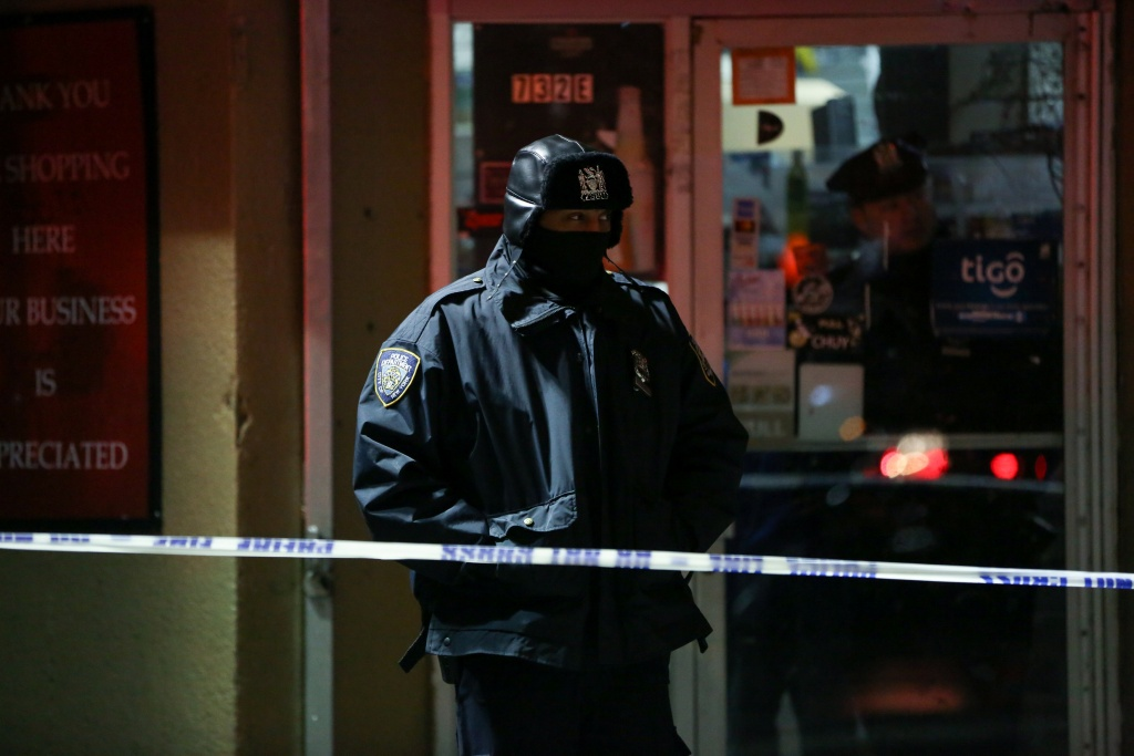 NYPD officers stand guard during an evacuation following a fire at an apartment building in New York