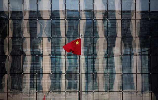A Chinese national flag flutters at the headquarters of a commercial bank on a financial street in central Beijing