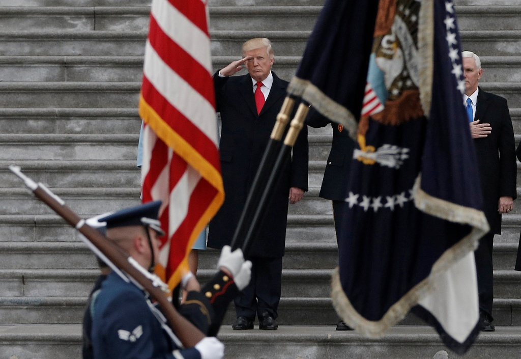 U.S. President Donald Trump salutes as he presides over a military parade following Trump's swearing-in ceremony in Washington