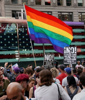 A rainbow flag flies as people protest U.S. President Donald Trump's ban on transgender individuals from serving in the U.S. military in New York City