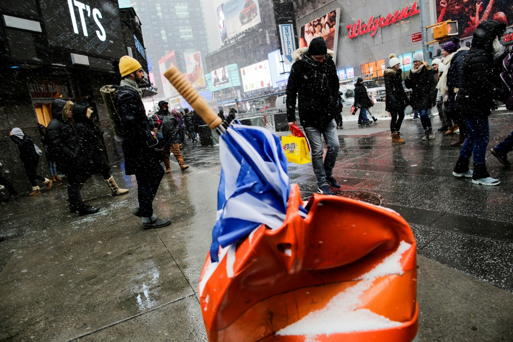 A damaged umbrella is seen in the trash can while people walk around Times Square, as a cold weather front hits the region, in Manhattan, New York