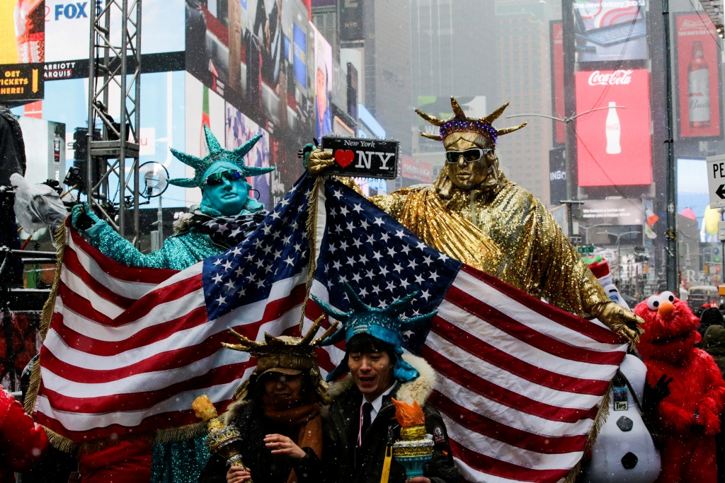 People dressed up as Statues of Liberty pose for pictures at Times Square during a snowfall, as a cold weather front hits the region, in Manhattan, New York