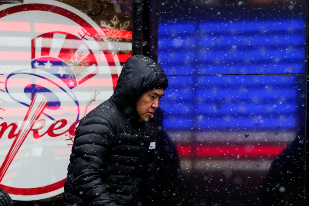 A man walks in falling snow at Times Square as a cold weather front hits the region, in Manhattan, New York