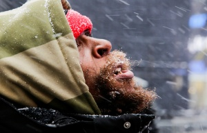A man looks at falling snow at Times Square as a cold weather front hits the region, in Manhattan, New York