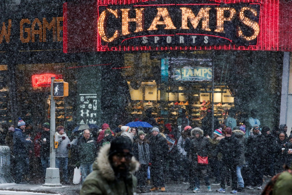 People walk around Times Square as a cold weather front hits the region, in Manhattan, New York