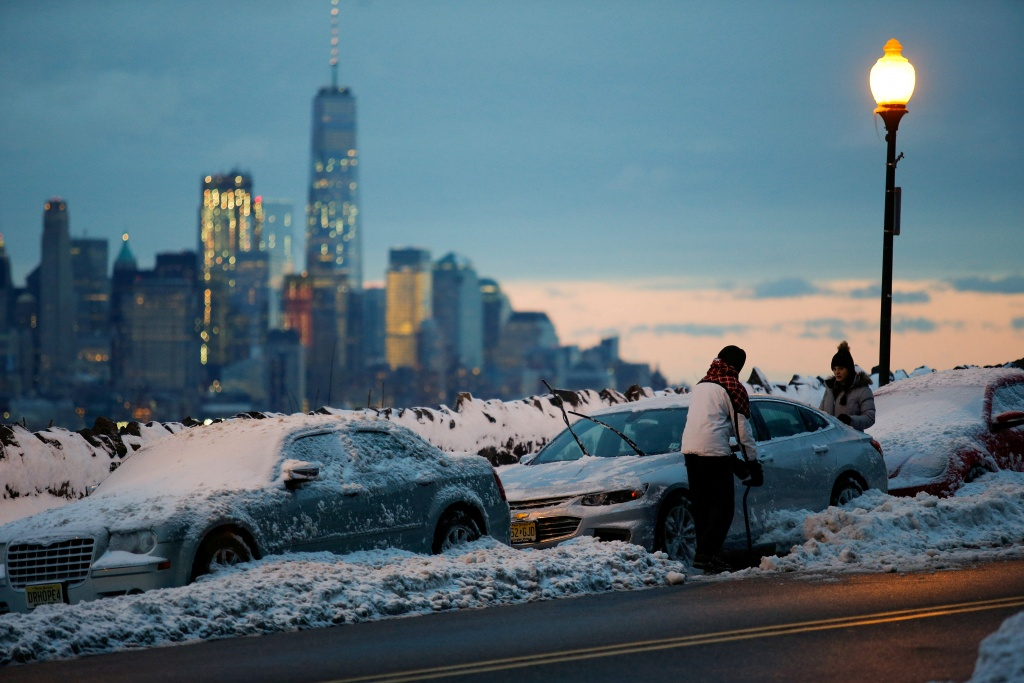 Residents clear their cars and street of snow in Weehawken
