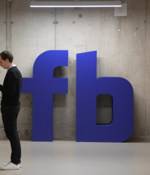 A man waits for an elevator in front of a logo at Facebook's headquarters in London