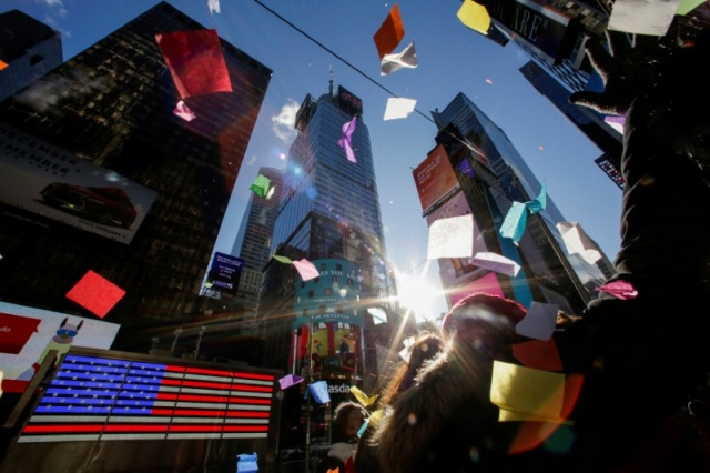 People look at confetti as it's thrown from the Hard Rock Cafe marquee in Times Square in New York City