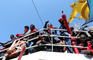 """Migrants wait to disembark from the Vos Hestia ship as they arrive at the Crotone harbour, after being rescued by a """"Save the Children"""" crew in the Mediterranean sea off the Libya coast, in Crotone"""