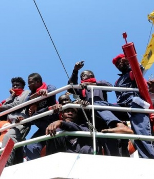 "Migrants wait to disembark from the Vos Hestia ship as they arrive at the Crotone harbour, after being rescued by a ""Save the Children"" crew in the Mediterranean sea off the Libya coast, in Crotone"