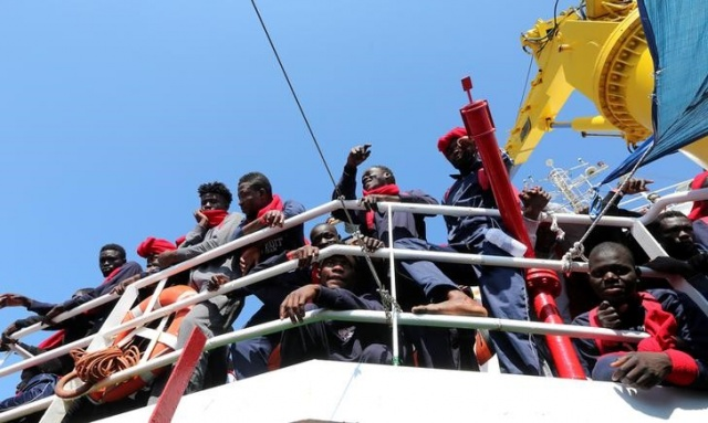 Migrants wait to disembark from the Vos Hestia ship as they arrive at the Crotone harbour, after being rescued by a