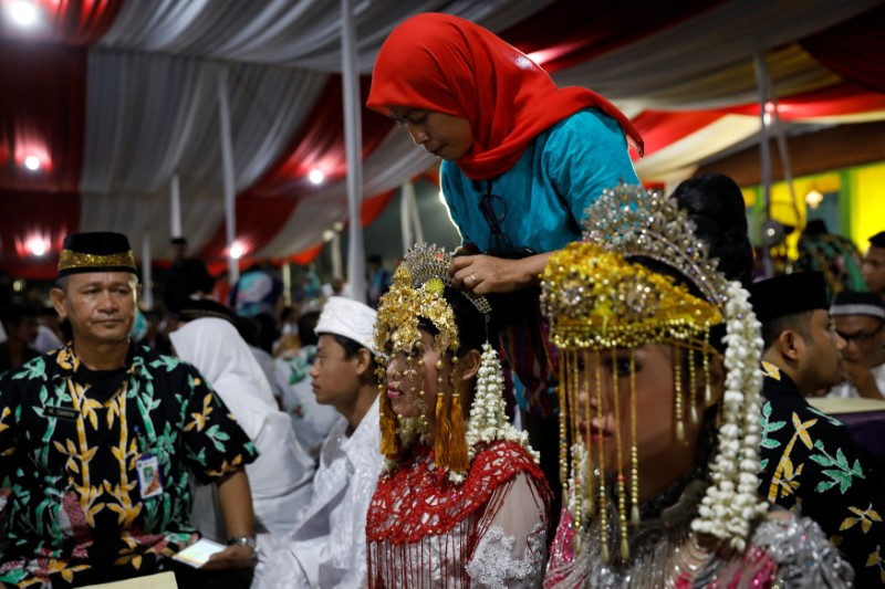 A bride has her headdress adjusted while taking part in a mass wedding organised by the city government as part of New Year's Eve celebrations in Jakarta