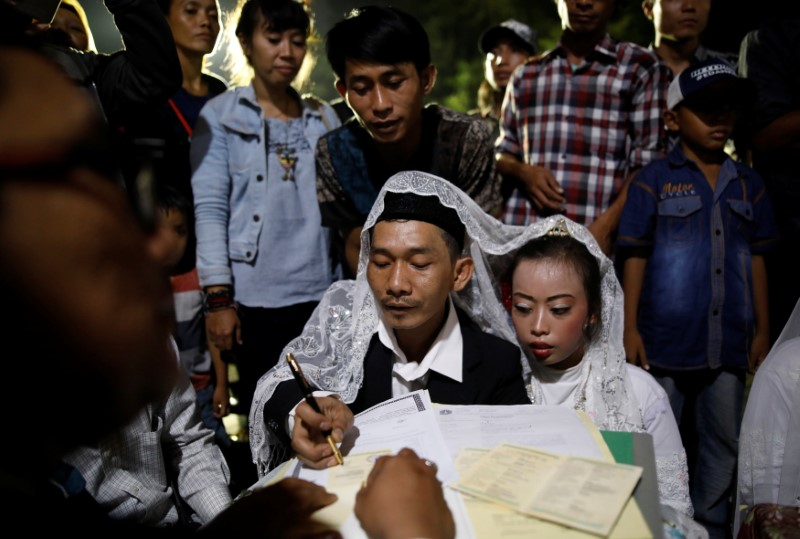 A couple takes part in a mass wedding organised by the city government as part of New Year's Eve celebrations in Jakarta