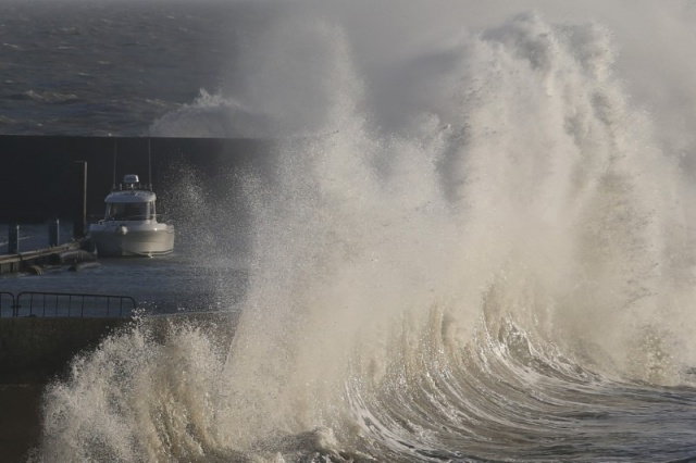 A high wave crashes on the protecting wall at the fishing harbour in Pornic