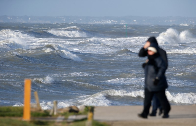 A couple walks near the beach as strong winds and high waves are seen at the Saint Gildas Point in Prefailles