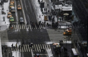 People cross 6th Avenue and 42nd Street as a cold weather front hits the region, in Manhattan, New York