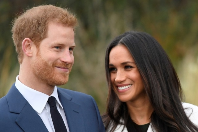 Britain's Prince Harry poses with Meghan Markle in the Sunken Garden of Kensington Palace in London