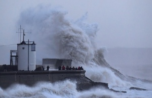 People view large waves and high winds associated with Storm Eleanor as they hit the lighthouse and seawall at Porthcawl