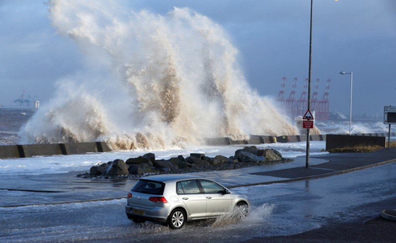 A car drives along a flooded road in New Brighton, on the coast of the Wirral peninsula, in Merseyside