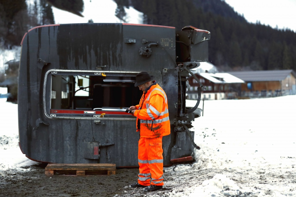 A worker inspects the carriage of the MOB train lying on its side, after if was pushed out of the tracks by gusts of wind during storm Eleanor near Lenk