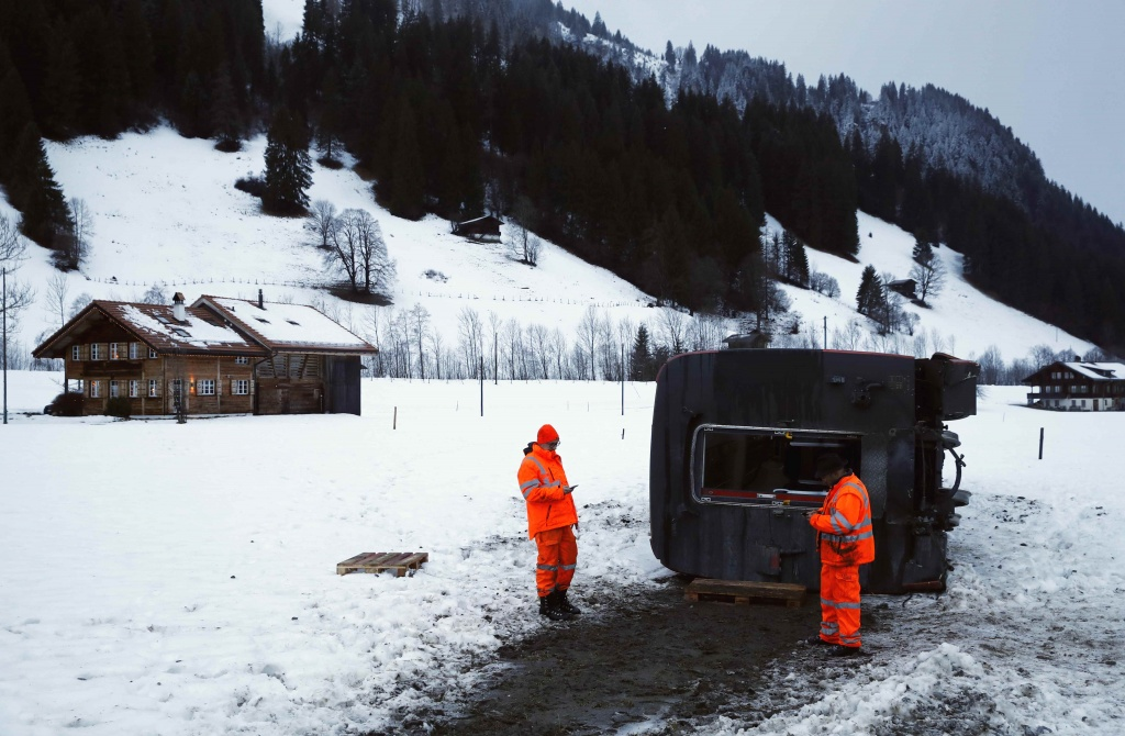 Workers inspect the carriage of the MOB train lying on its side, after if was pushed out of the tracks by gusts of wind during storm Eleanor near Lenk