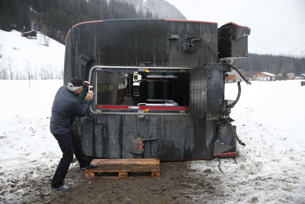 A man takes pictures of a carriage of the MOB train lying on its side after if was pushed out of the tracks by gusts of wind during storm Eleanor near Lenk