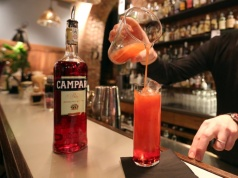 "A barman prepare a "" Campari orange"" cocktail in a bar downtown Milan"