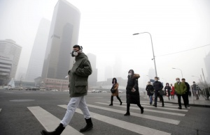 A man wearing a respiratory protection mask walks toward an office building during smog in Beijing