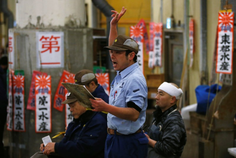 An auctioneer raises his hand as he starts the New Year's auction of the frozen tuna at the Tsukiji fish market in Tokyo