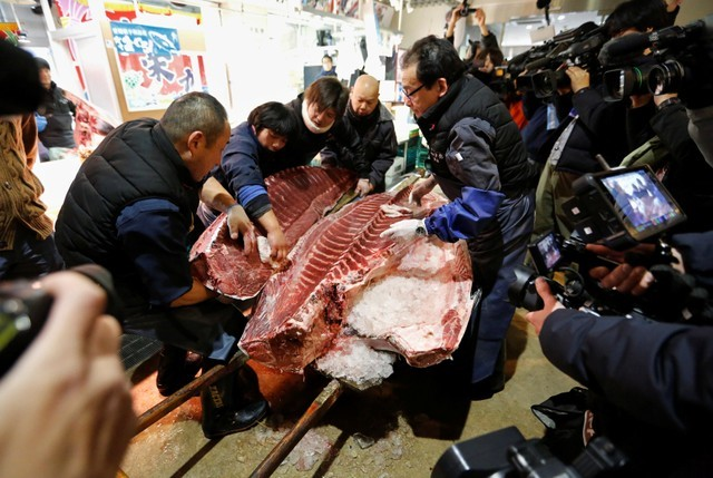 Fishmongers hold a 405 kg bluefin tuna as they cut it in front of their store outside Tsukiji fish market in Tokyo