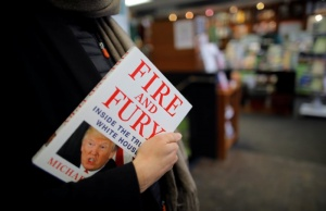 """A woman holds a copy of the book """"Fire and Fury: Inside the Trump White House"""" by author Michael Wolff are seen at a local book store in Washington, DC"""