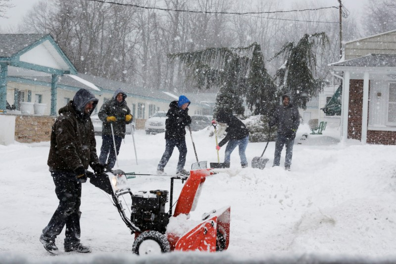 People clean the path during Storm Grayson at the Jersey shore in Monmouth Beach, New Jersey