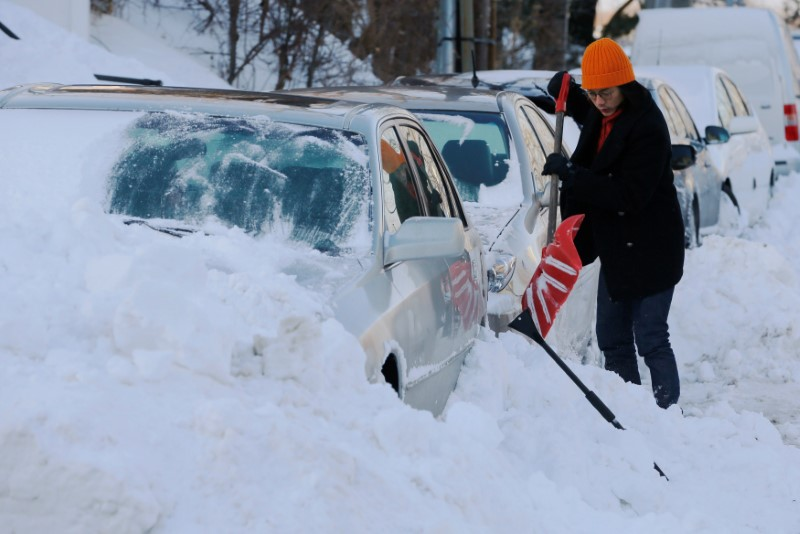 A woman digs out her car following winter snow storm Grayson in Boston