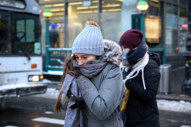 A woman bundles up against the cold temperature as she walks in New York