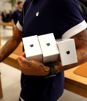 An Apple Store staff shows Apple's new iPhones X after they go on sale at the Apple Store in Regents Street London