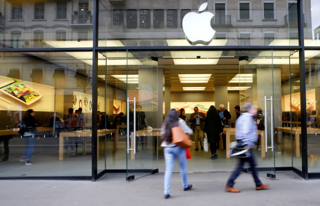 People walk in front of a branch of U.S. technology company Apple in Zurich