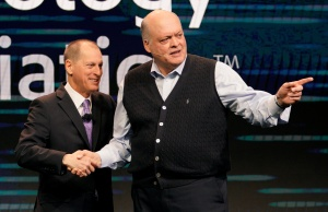 Gary Shapiro, CEO of the Consumer Technology Association shakes hands with Jim Hackett, CEO of Ford Motor Company, at CES in Las Vegas