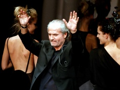 Italian designer Gianni Versace waves at the end of his presentation of his spring-summer '97 ready-to-wear collection at a Milan fashion show, in Milan