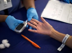A person receives a test for diabetes during Care Harbor LA free medical clinic in Los Angeles