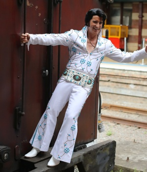 An Elvis Presley impersonator hangs from the Elvis Express train at Sydney's Central station before it departs for the 26th annual Elvis Festival
