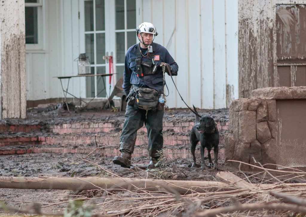 A search and rescue worker with a dog scours through properties after a mudslide in Montecito,