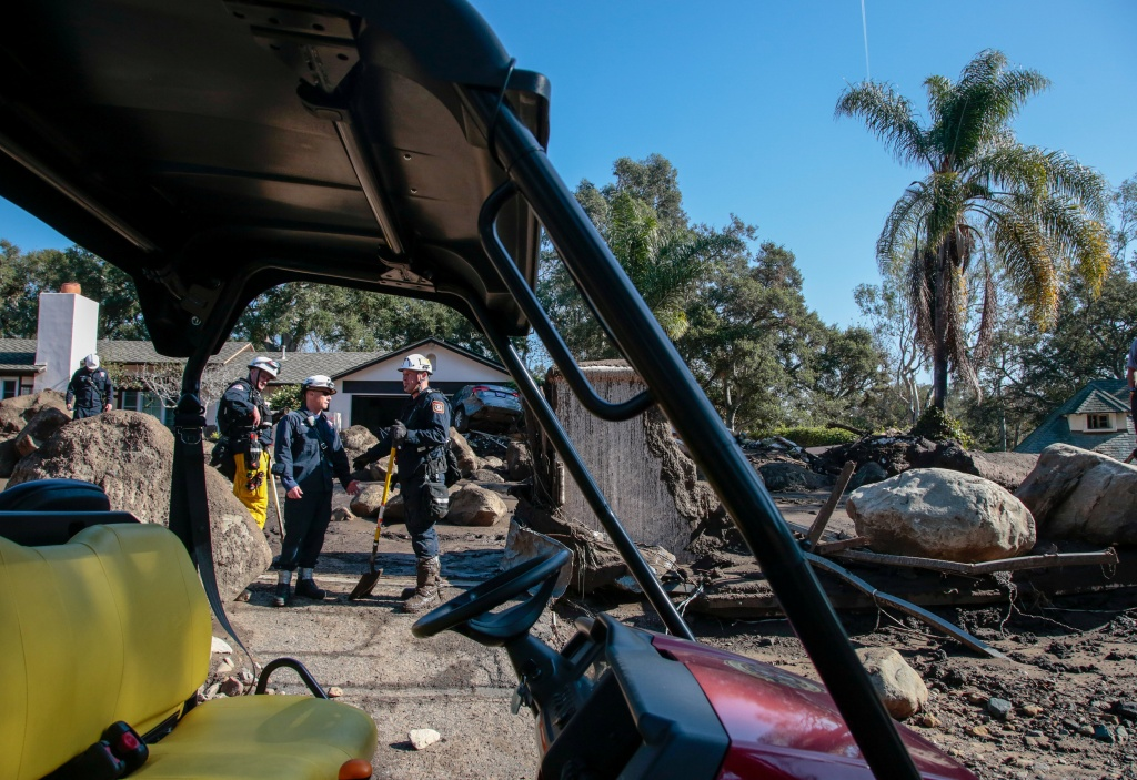 Search and rescue workers scour through properties after a mudslide in Montecito